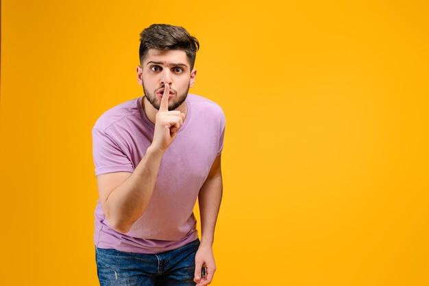 Jovem mostrando gesto silencioso isolado sobre fundo amarelo