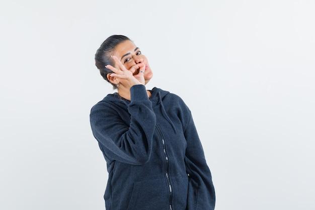 Jovem, mostrando gesto zip na jaqueta e procurando segredo. vista frontal.
