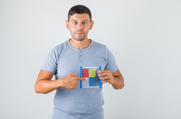 Jovem mostrando o ábaco colorido na mão em uma camiseta cinza
