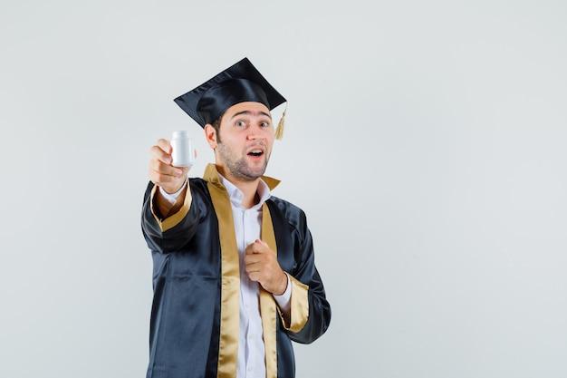 Jovem mostrando o frasco de comprimidos em uniforme de pós-graduação e parecendo feliz, vista frontal.