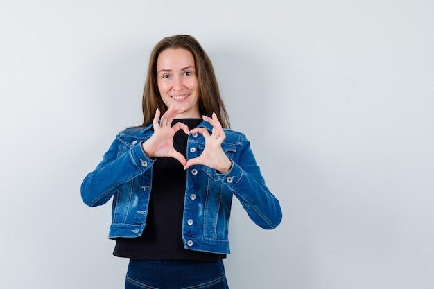 Jovem, mostrando o gesto de coração na blusa, jaqueta e olhando alegre, vista frontal.