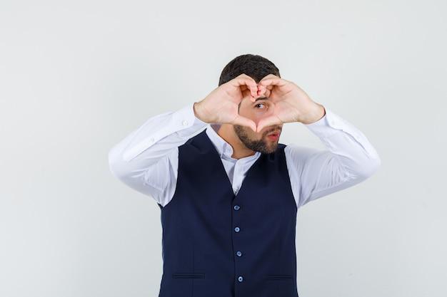 Jovem, mostrando o gesto de coração na camisa e vista frontal do colete.
