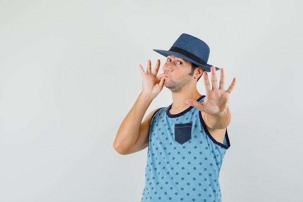 Jovem mostrando o gesto de parada com a boca fechada como zíper na camiseta azul, chapéu e olhando com medo, vista frontal.