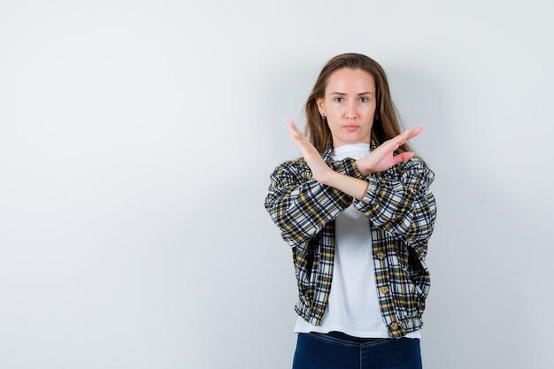 Jovem, mostrando o gesto de parada em t-shirt, jaqueta e olhando resoluta, vista frontal.