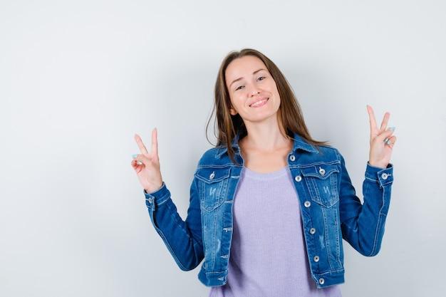 Jovem, mostrando o gesto de paz em t-shirt, jaqueta e olhando alegre, vista frontal.