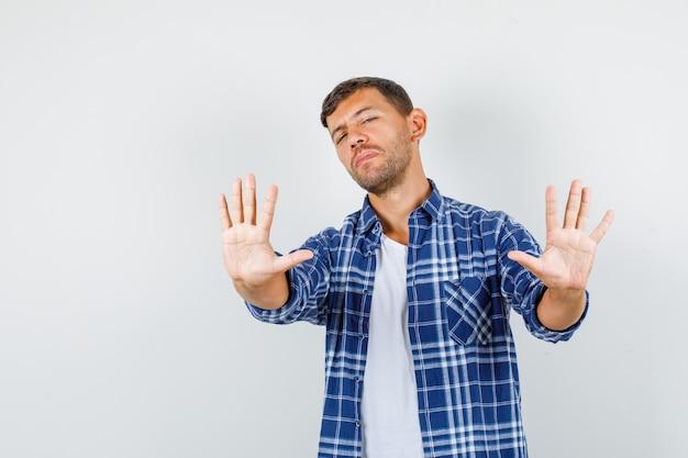 Jovem, mostrando o gesto de recusa na camisa e olhando com nojo, vista frontal.