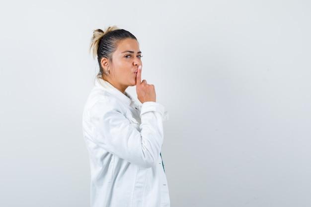 Jovem, mostrando o gesto de silêncio na camisa, jaqueta branca e olhando cuidadoso. vista frontal.