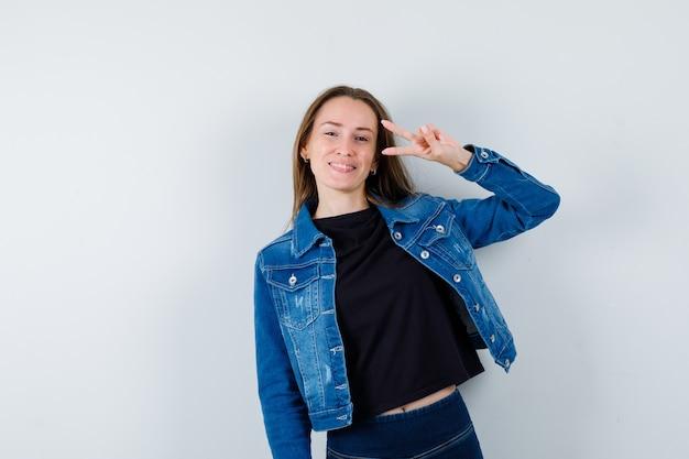 Jovem, mostrando o gesto de vitória na blusa, jaqueta e olhando confiante, vista frontal.