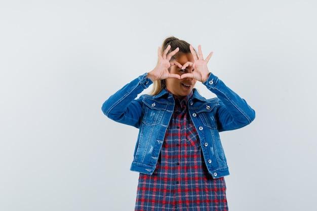 Jovem, mostrando o gesto do coração na camisa, jaqueta e olhando feliz, vista frontal.