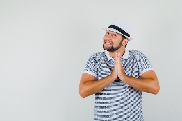 Jovem mostrando o gesto namaste em t-shirt, chapéu e olhando alegre, vista frontal.