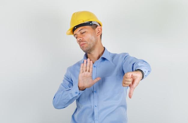 Jovem mostrando o polegar para baixo e gesto de parada na camisa, capacete