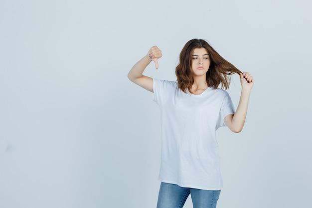 Jovem, mostrando o polegar para baixo, segurando uma mecha de cabelo em uma camiseta, jeans e parecendo descontente, vista frontal.