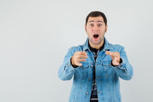 Jovem mostrando óculos em t-shirt, jaqueta e olhando espantado, vista frontal.