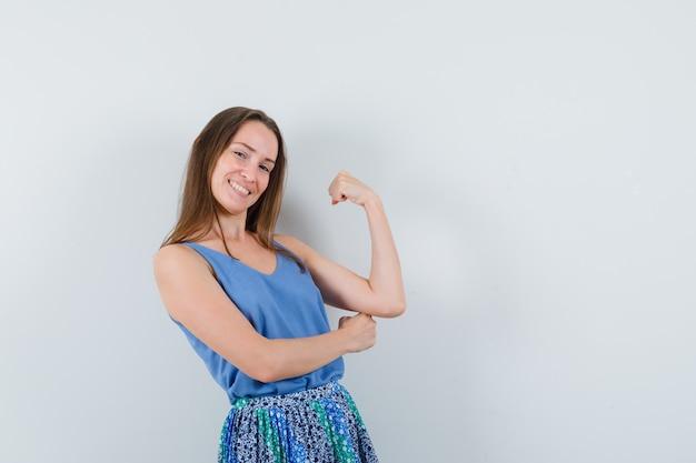 Jovem mostrando os músculos do braço em camiseta, saia e parecendo feliz, vista frontal.