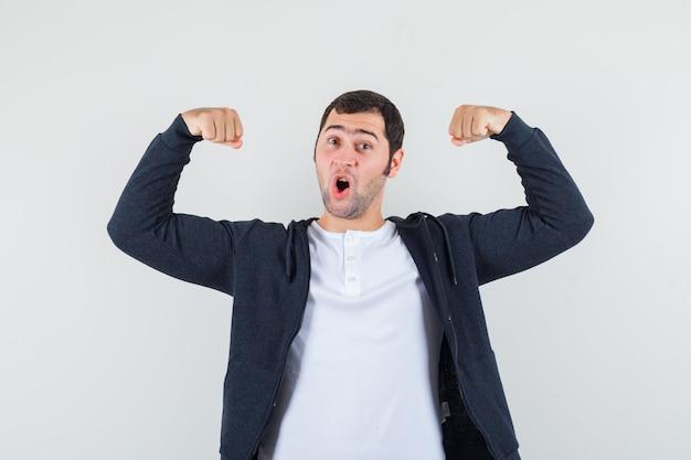 Jovem mostrando os músculos em uma camiseta branca e um capuz preto com zíper na frente e parecendo otimista, vista frontal.