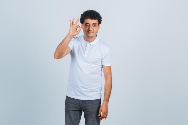 Jovem mostrando sinal de ok e piscando em jeans e camiseta branca e parecendo feliz. vista frontal.