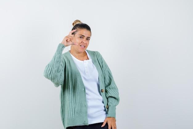 Jovem mostrando tamanho pequeno assinar em camiseta, jaqueta e parecendo confiante