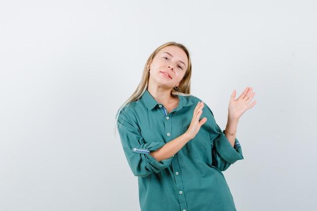 Jovem mostrando um gesto de boas-vindas com uma camisa verde e parecendo confiante