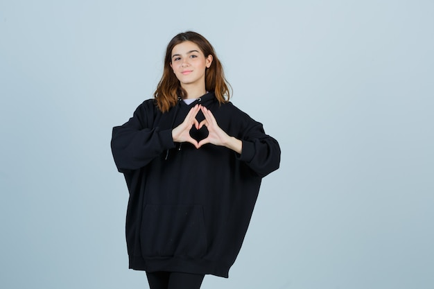 Jovem, mostrando um gesto de coração com um capuz enorme, calças e uma aparência bonita. vista frontal.