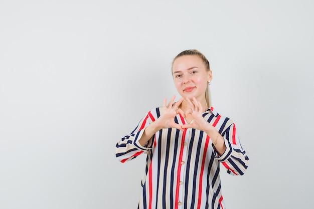Jovem mostrando um gesto de coração em uma camisa listrada e parecendo alegre