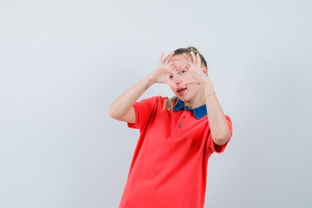 Jovem mostrando um gesto de coração em uma camiseta e parecendo jovial