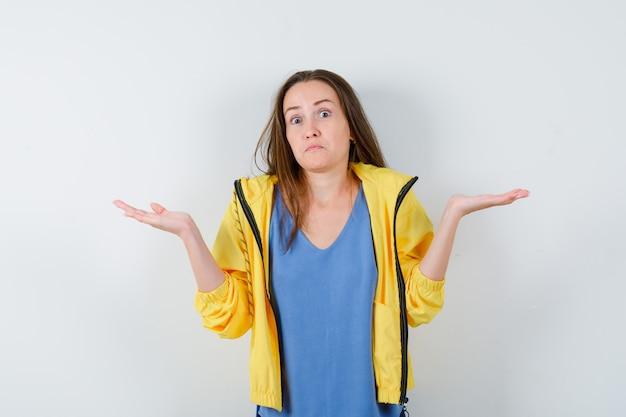 Jovem, mostrando um gesto desamparado em t-shirt, jaqueta e parecendo confuso. vista frontal.