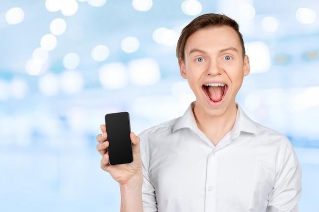Jovem mostrando uma tela do telefone inteligente em branco