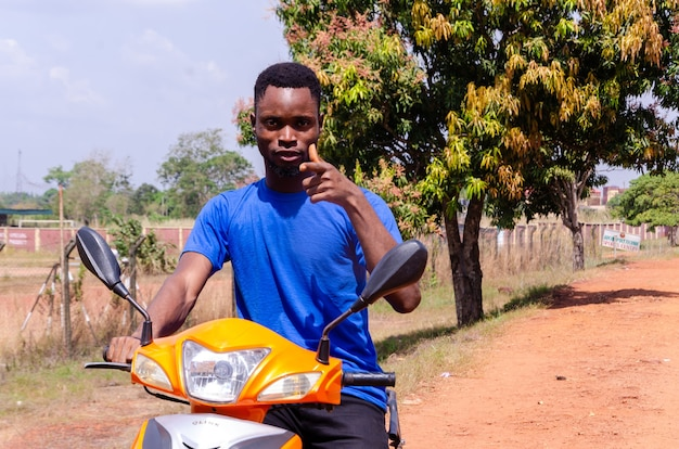 Jovem motociclista africano animado apontando