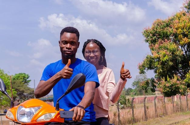 Jovem motociclista africano bonito e seu cliente empolgados e fazendo sinal de positivo