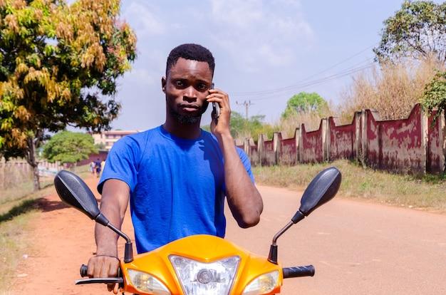 Jovem motociclista africano bonito fazendo ligações enquanto espera o cliente chegar