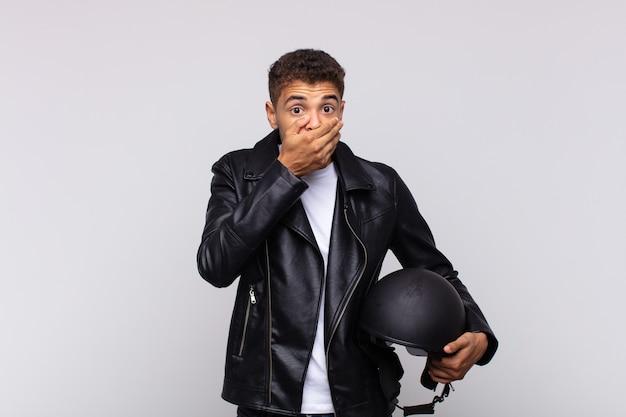 Jovem motociclista cobrindo a boca com as mãos com uma expressão chocada e surpresa, mantendo um segredo ou dizendo oops