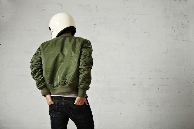 Jovem motociclista com capacete branco e retrato de jaqueta verde na parte de trás com as mãos nos bolsos de trás da calça jeans com paredes brancas.