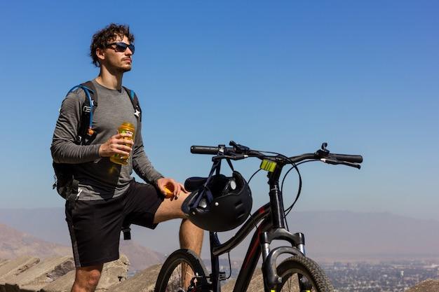 Jovem motociclista com óculos de sol segurando uma garrafa de água ao lado de mountain bike em um dia ensolarado