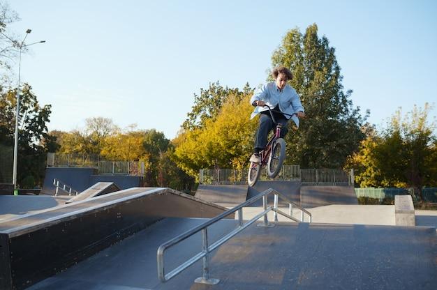 Jovem motociclista de bmx cavalga por trilhos no skatepark. esporte radical de bicicleta, truque de ciclismo perigoso, passeios de rua, ciclismo no parque de verão