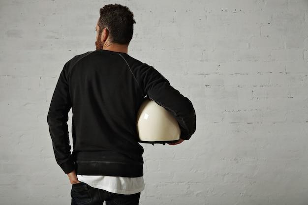 Jovem motociclista em forma de moletom preto e jeans segurando um capacete branco na lateral do corpo com paredes de tijolos pintados