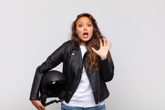 Jovem motociclista gritando com as mãos para o alto, sentindo-se furiosa, frustrada, estressada e chateada