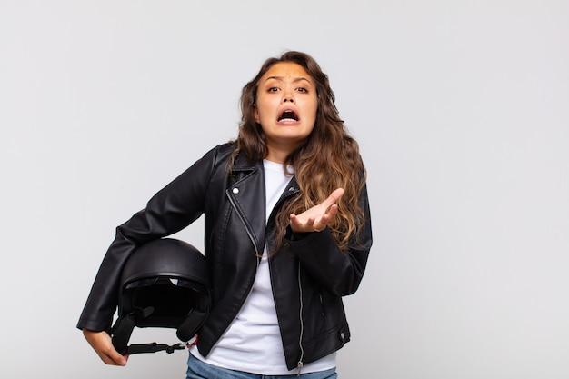Jovem motociclista parecendo desesperada e frustrada, estressada, infeliz e irritada, gritando e gritando