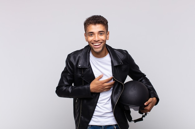 Jovem motociclista rindo alto de uma piada hilária, sentindo-se feliz e alegre, se divertindo