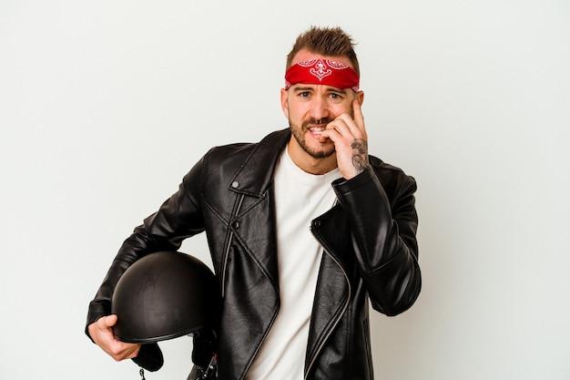 Jovem motociclista tatuado homem caucasiano segurando um capacete isolado no fundo branco, roendo as unhas, nervoso e muito ansioso.