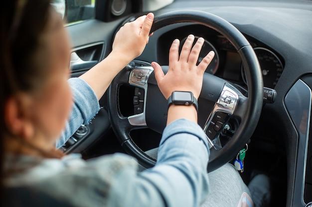 Jovem motorista agressiva usando buzina ou trompete para os outros carros, motorista perigosa
