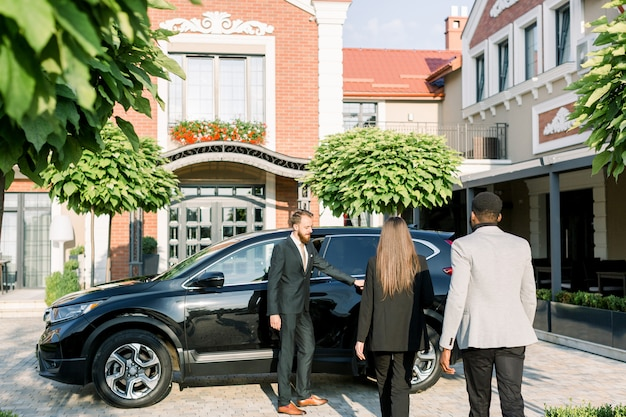 Jovem motorista caucasiano ou parceiro de terno, abrindo a porta do carro para o empresário africano e empresária caucasiana, vista traseira
