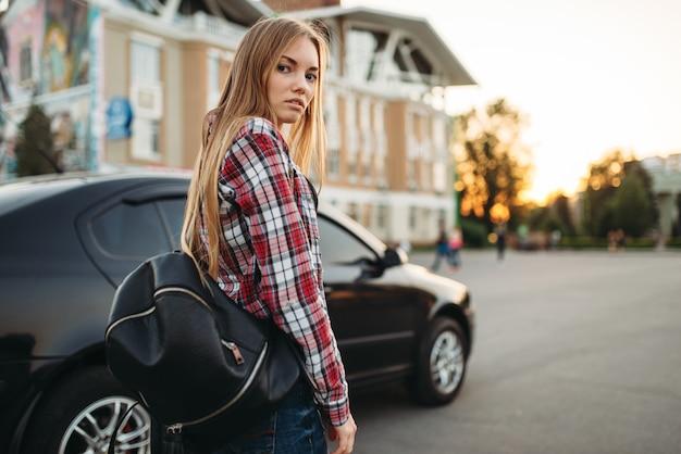 Jovem motorista com uma bolsa contra um carro