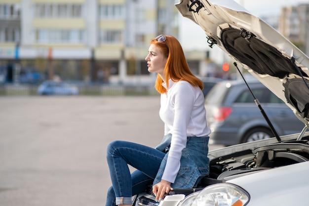 Jovem motorista de mulher estressada perto de um carro quebrado com capô estourado, esperando por ajuda.