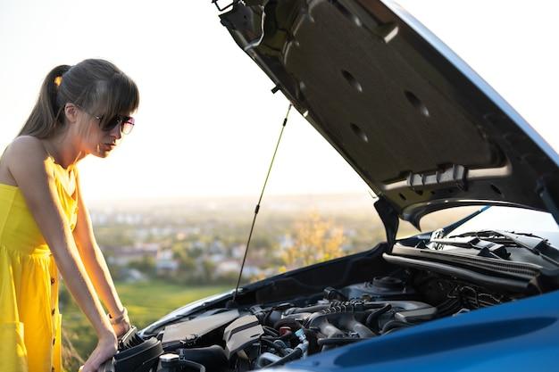 Jovem motorista de mulher intrigada em pé perto de seu carro com capô levantado olhando para o motor quebrado.