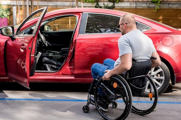 Jovem motorista deficiente entrando em cadeira de rodas de carro vermelho.