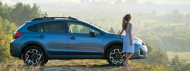 Jovem motorista do sexo feminino descansando perto de seu carro, aproveitando a noite quente de verão. conceito de viagens e fuga.