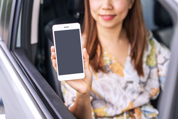 Jovem motorista do sexo feminino sentada em um carro e mostrando uma tela vazia do telefone inteligente