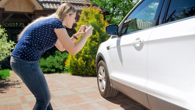 Jovem motorista do sexo feminino tirando fotos de seu carro para anúncio de venda.