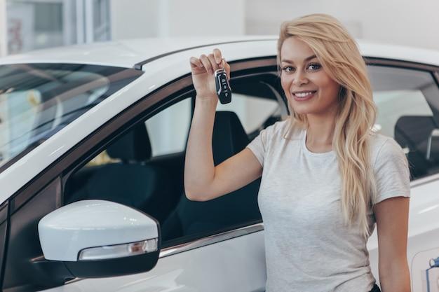 Jovem motorista segurando a chave do carro posando perto de seu novo automóvel na concessionária