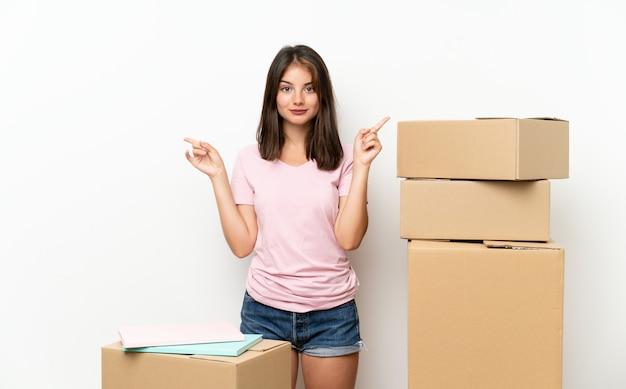 Jovem, movendo-se em nova casa entre caixas apontando para as laterais, tendo dúvidas